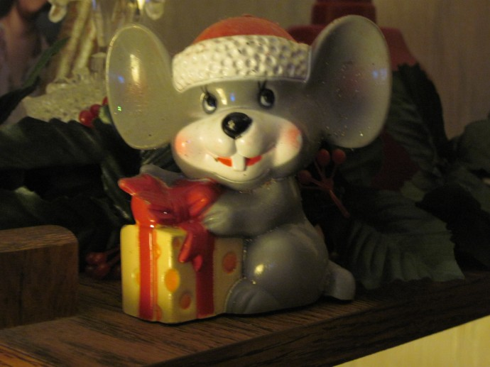 It's an adorable mouse in a Santa hat with a cheese gift!