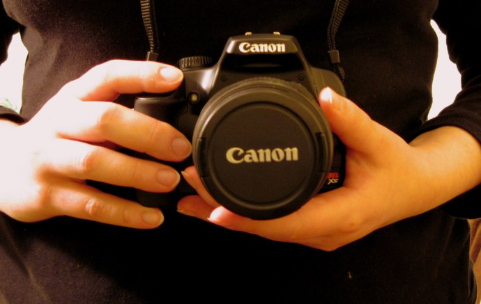 Me, holding my new camera baby, a Canon EOS Rebel XS with EF-S 18-55 mm IS lens.